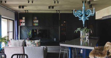 Островът с мивка и маса за хранене и дневната се проектират върху графитената стена с телевизор, шкафове и етажерка. Деликатни акценти са цветовете в текстила. Полилей от Moooi